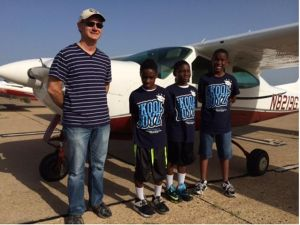 A Local EAA Pilot alongside three students.