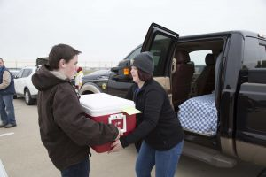Volunteers load cars with meals ready to be delivered during the Meals on Wheels Blitz