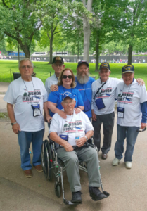 Dennis DeFrank and his wife Lisa (in blue SWA shirts) and five Veterans on a May 14 Honor Flight trip to the Vietnam Wall in background.