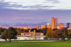 32845654 - denver colorado skyline from city park with city park boathouse and rocky mountains in background on autumn morning