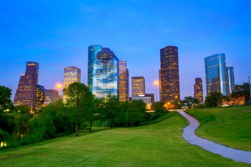 22531601 - houston texas modern skyline at sunset twilight from park lawn