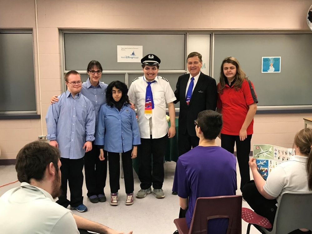 Craig pictured with students wearing Southwest Flight Attendant and Pilot uniforms