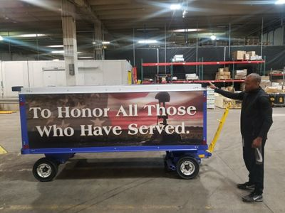 Andre Sims, Cargo Customer Service Manager, stands next to the decorated MHR cart in Atlanta