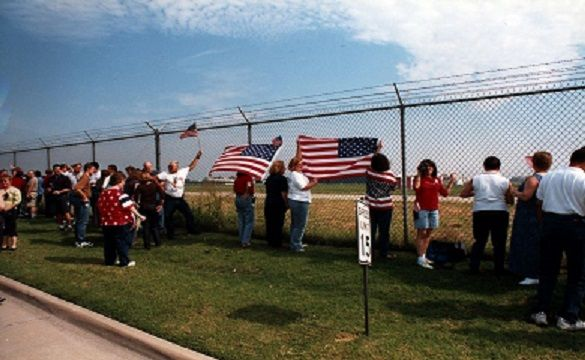 Employees line the fence at Southwest Headquarters to watch the first flight take off from Dallas Love Field (DAL) after the 9/11 terrorist attacks