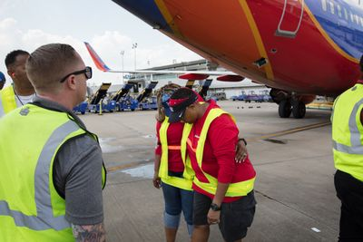 Southwest Airlines Houston-based flight crews arrive Houston Hobby Airport after being stuck in other cities during Hurricane Harvey on Friday, September 1, 2017. In lieu of a water cannon arch, the ground ops supervisors made a salute with a wall of belt loaders. Photo by Stephen M. Keller