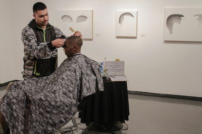 Jose Flores, Barber, cuts hair at opening of Custom Lives, art by Nery Gabriel Lemus in background. Photo by Damian Kelly.